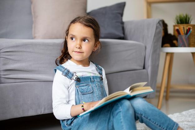 책에서 읽는 방법을 배우는 어린 소녀