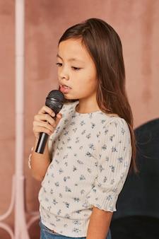 Маленькая девочка учится петь дома с микрофоном
