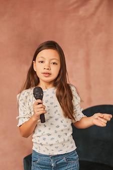 Маленькая девочка учится петь дома