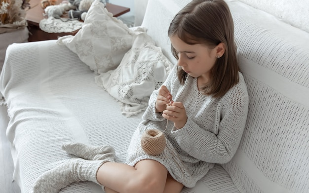 Little girl learning to knit, home leisure and needlework concept.