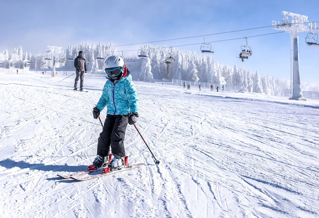 Little girl learning to ski at the mountain resort with ski lift