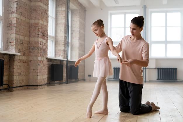 Маленькая девочка учится танцевать балет с помощью своего тренера в танцевальной студии