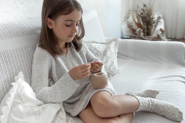 Маленькая девочка учится вязать, домашний отдых и концепция рукоделия.