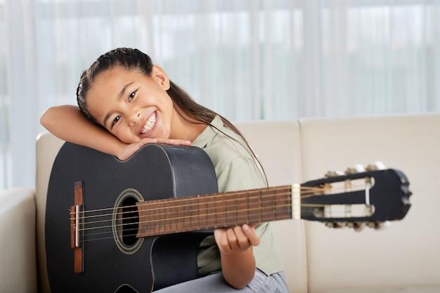 Маленькая девочка учится играть на гитаре