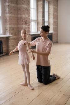 Маленькая девочка учится стоять в правильном положении во время занятий балетом с тренером