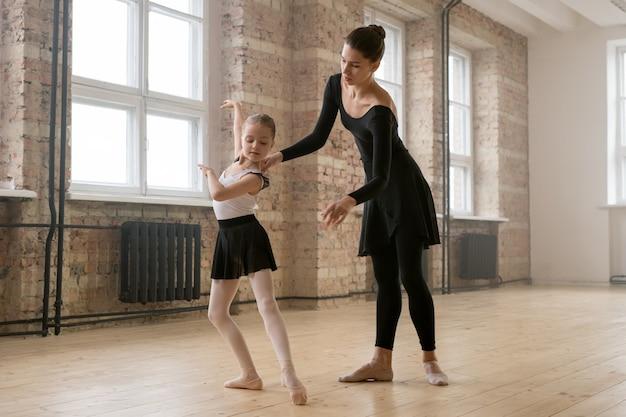 トレーナーとバレエのクラスで正しい位置に立つことを学ぶ少女