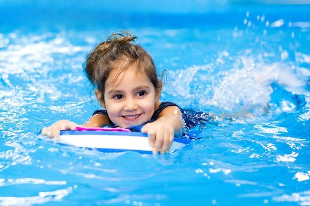 プールで泳ぐことを学ぶ少女