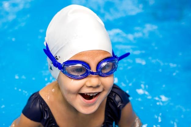 Маленькая девочка учится плавать в бассейне