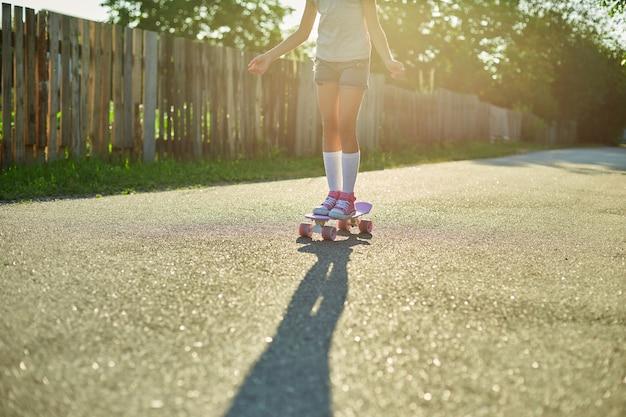 스케이트보드 사용법을 배우는 어린 소녀, 여름 도시의 시골 거리에서 스케이트보드를 타는 흰색 양말과 분홍색 신발을 신은 익명의 아이.