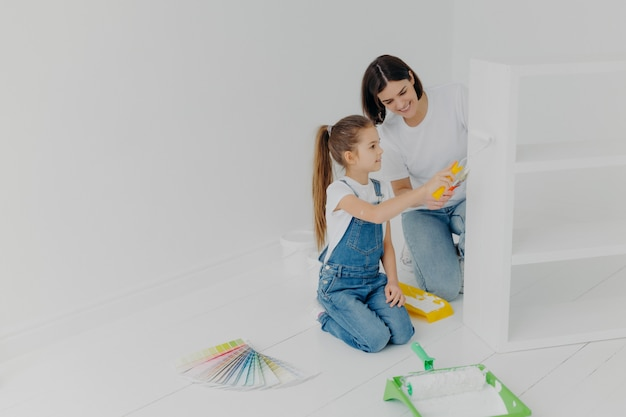 Little girl learns how to paint with roller