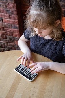A little girl learns notes in a playful way, with the help of a piano on her phone