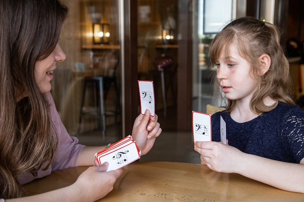 A little girl learns notes in a playful way, with the help of special musical cards
