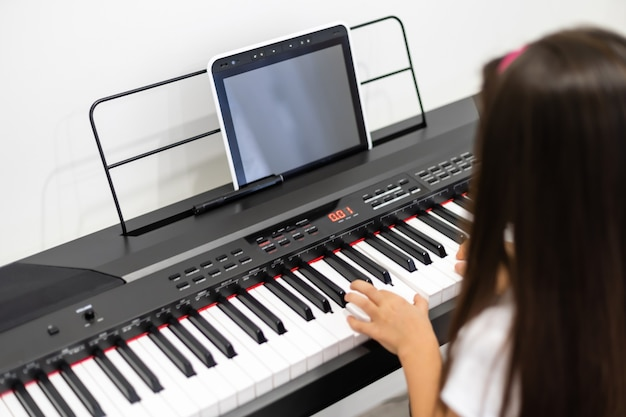 A little girl learns to play the piano from video lessons