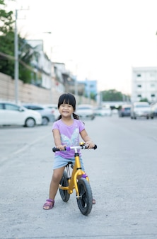 Little girl learns to riding balance bike on the road