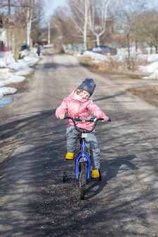 어린 소녀는 마을의 도로에서 안전 바퀴가 달린 자전거를 타는 법을 배웁니다.