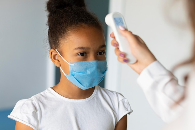 Little girl letting someone to take her temperature