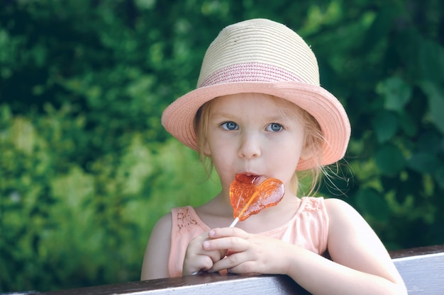 The little girl licks the lollipop. a beautiful child in a straw hat.