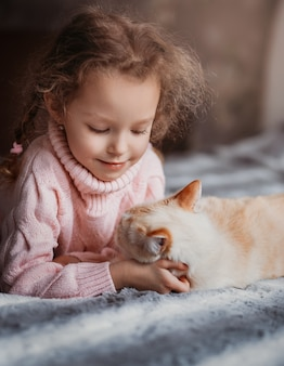 A little girl lies on a bed with a cat