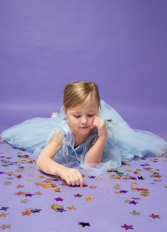 A little girl lies on the floor and plays with confetti on purple