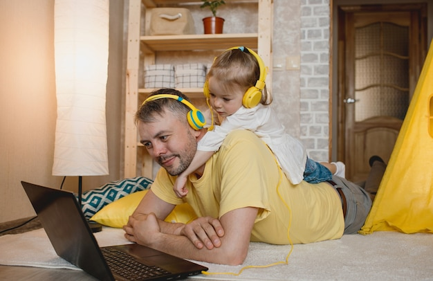 A little girl lies on her father's back and listens to music with yellow headphones while looking at her laptop. the concept of family happiness