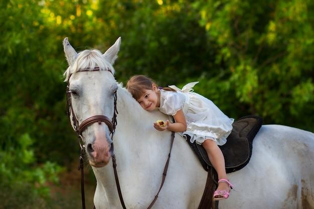 The little girl lies on a horse
