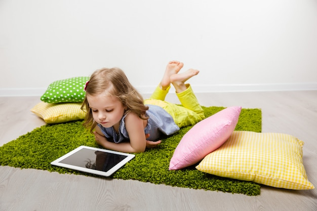 The little girl lies on a rug, watches the tablet.