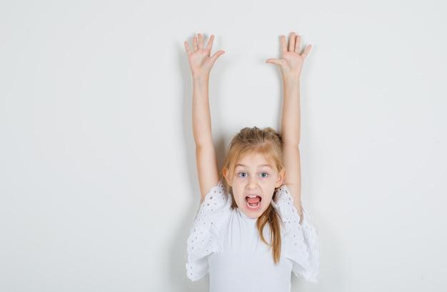 白いtシャツで手を持ち上げて驚いて見ている少女