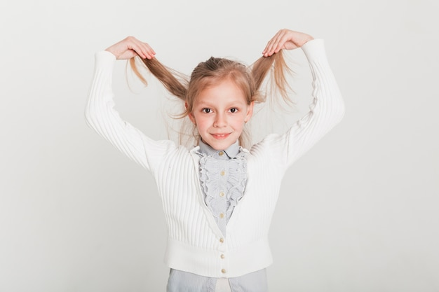 Little girl lifting her hair