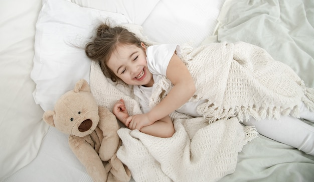 Little girl in light pajamas on the bed close up.