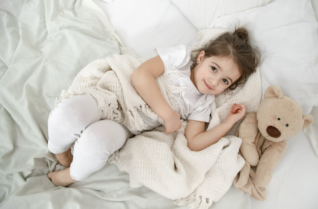 Little girl in light pajamas on the bed