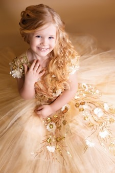 Little girl like a doll with curly golden hair in nice gold dress