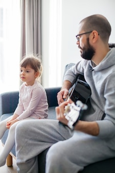 Little girl listening her father playing guitar for her