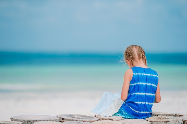 Little girl listening to music on headphones on caribbean beach