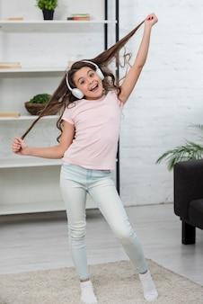 Little girl listening music on headphones