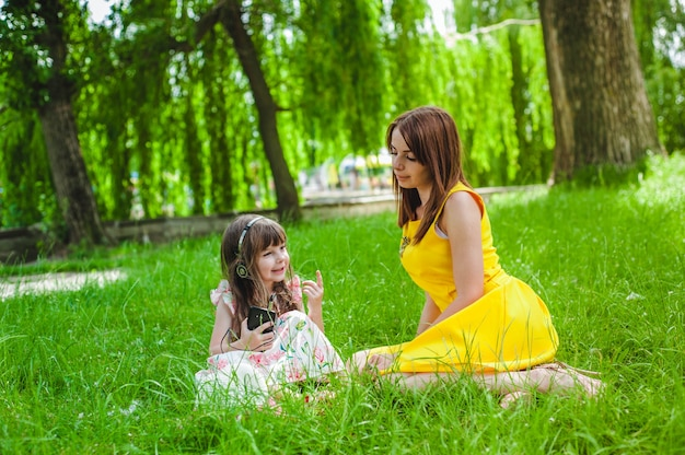 Little girl listening to music and her mother watches her
