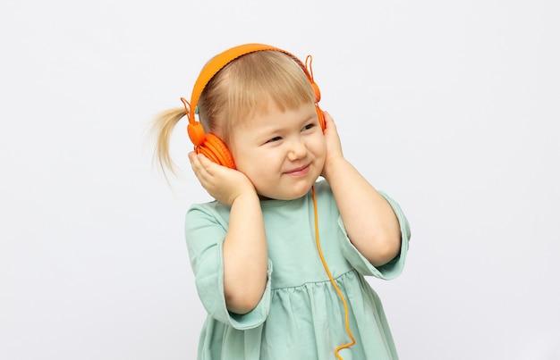 Little girl listening to music indoor.