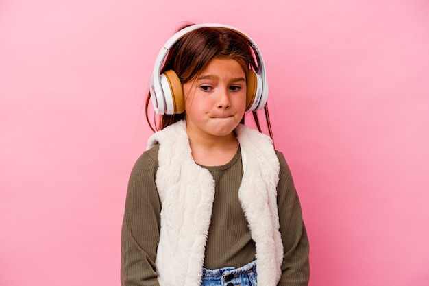 분홍색 벽에 고립 된 어린 소녀 듣기 음악은 혼란스럽고 의심스럽고 확신이 없습니다.