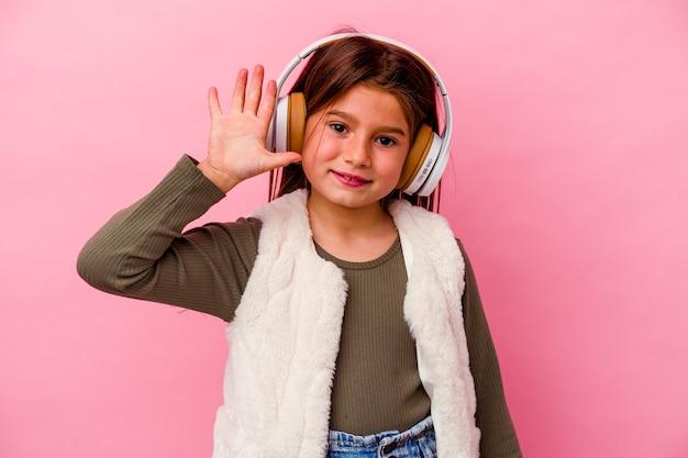 핑크 벽에 고립 된 어린 소녀 듣기 음악 손가락으로 명랑 보여주는 5 번 미소