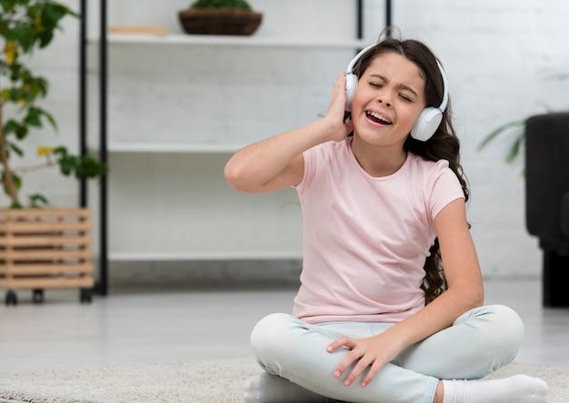 Little girl listening music through headphones indoors