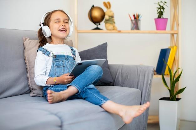 Little girl listening to music through headphones