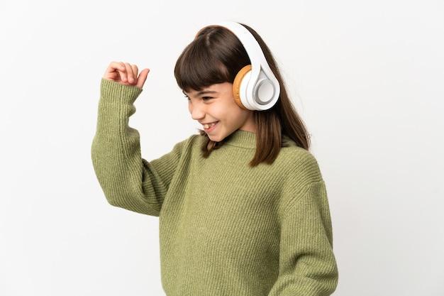 音楽を聴いて踊る白い背景で隔離の携帯電話で音楽を聴く少女