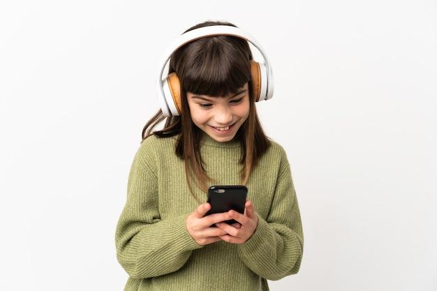Маленькая девочка слушает музыку с мобильным телефоном, изолированным на белом фоне, слушает музыку и смотрит на мобильный