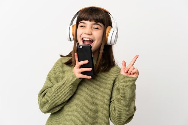 Маленькая девочка слушает музыку с помощью мобильного телефона, изолированного на белом фоне, слушает музыку с помощью мобильного телефона и поет