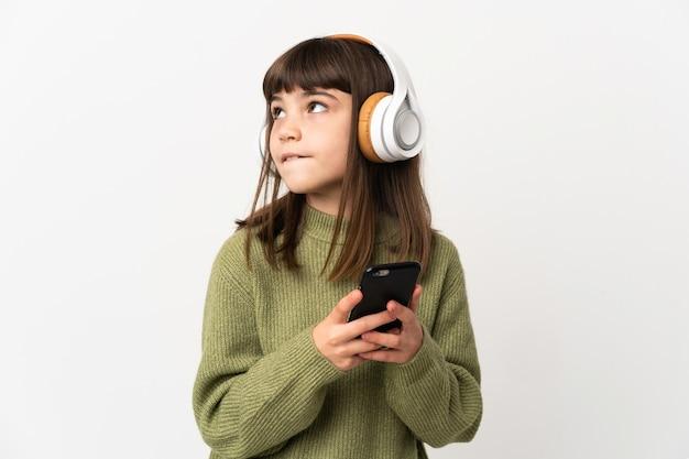 白い背景で隔離の携帯電話で音楽を聴いている少女携帯電話で音楽を聴いて考えている