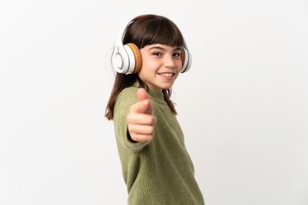 흰 벽에 음악을 듣고 앞을 가리키는 모바일로 음악을 듣고 어린 소녀