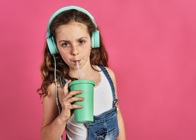 Little girl listening to music with headphones and drinking a juice on a pink background