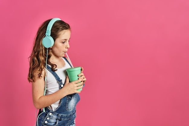 Little girl listening to music with headphones and drinking a juice on a pink wall
