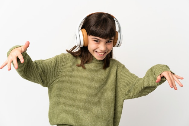 Little girl listening music with a mobile isolated on white background listening music and dancing