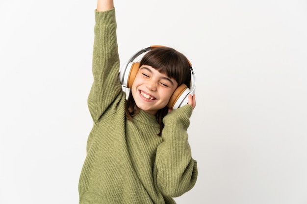 Little girl listening music with a mobile isolated on white wall listening music and dancing