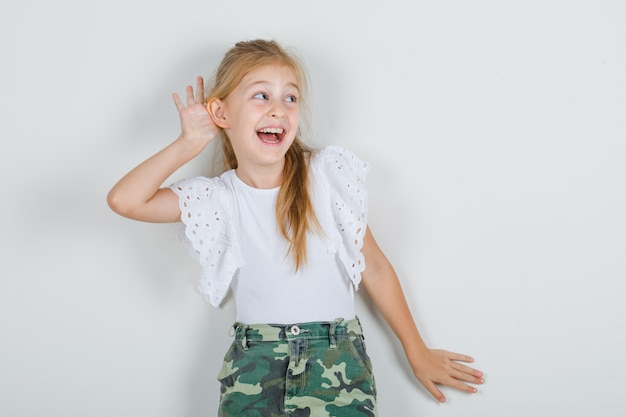 Little girl listening something with hand over ear in white t-shirt
